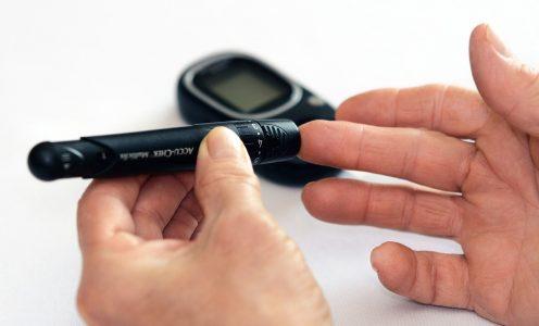 Pessoa mede glicemia no dedo com aparelho