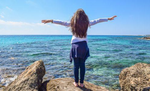 Menina de braços abertos em frente ao mar