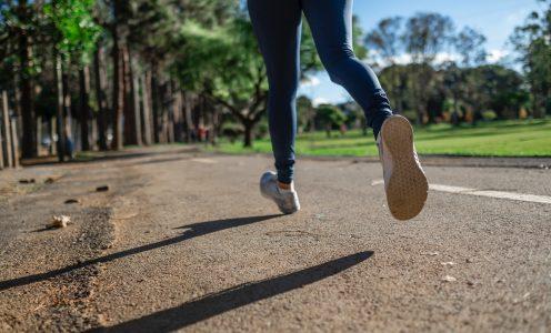 Pernas de pessoa correndo em um ambiente arborizado